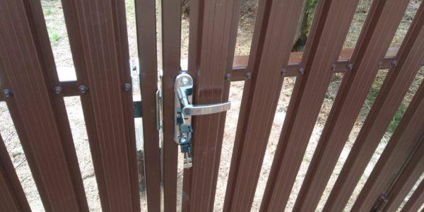 Забор из металлического штакетника с дверной ручкой